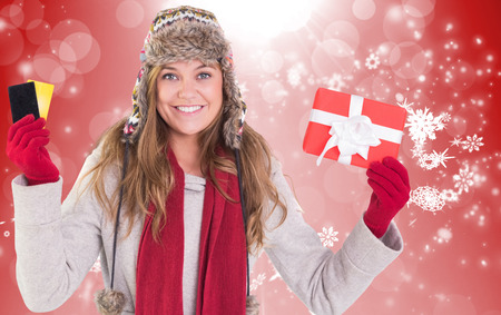 Happy blonde in winter clothes holding gifts against red design with white snowflakes photo