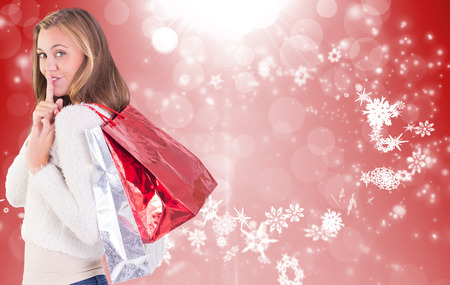 Pretty blonde keeping a secret holding bags against red design with white snowflakes photo