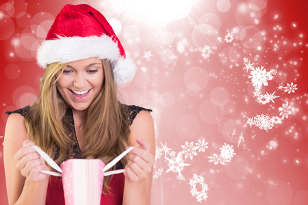 Festive blonde opening a gift bag against red design with white snowflakes photo