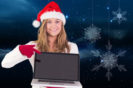 Festive blonde pointing to laptop against snowflakes hanging against starry sky photo