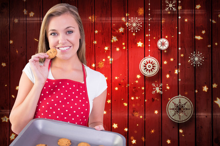 Pretty homemaker showing hot cookies against christmas decorations over wood photo