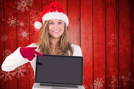 Festive blonde pointing to laptop against snowflake pattern on red planks photo