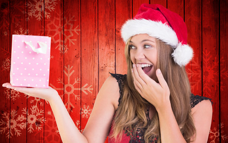Festive blonde holding a gift bag against snowflake pattern on red planks photo