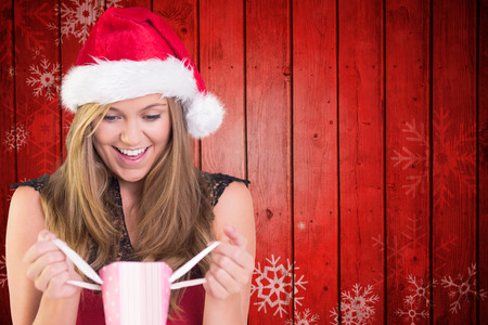 Festive blonde opening a gift bag against snowflake pattern on red planks photo