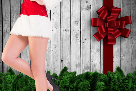 Festive womans legs in high heels against digitally generated fir tree branches photo
