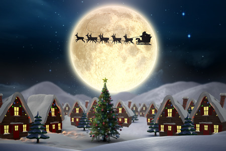 Cute christmas village against stars twinkling in night sky photo
