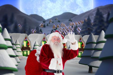 Santa claus waving against quaint town with bright moon photo