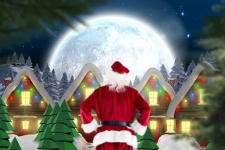 Santa Claus against quaint town with bright moon photo
