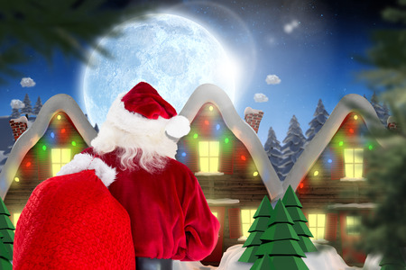 Santa claus carrying sack against quaint town with bright moon photo