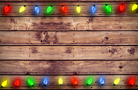 Christmas lights in a line against wooden planks background photo
