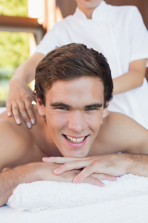 Close up of a handsome young man receiving shoulder massage at spa center photo