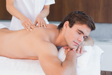 woman massage: View of a young man receiving back massage at spa center