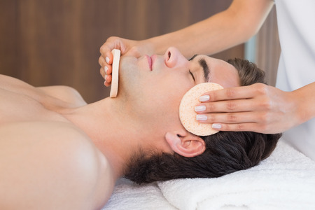 male facial: Close -up of a handsome young man receiving facial massage at spa center Stock Photo
