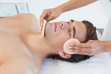 facial spa: Close -up of a handsome young man receiving facial massage at spa center Stock Photo
