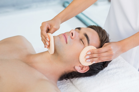 adult massage: Close -up of a handsome young man receiving facial massage at spa center Stock Photo