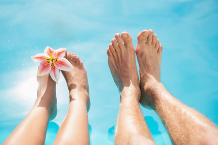 Close up of couples bare feet against swimming pool on a sunny day photo