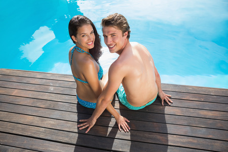 Rear view portrait of a romantic young couple by swimming pool on a sunny day photo