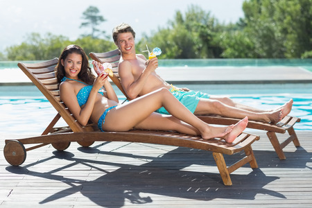 Full length of a young couple sitting on sun loungers by swimming pool photo