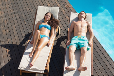 loungers: Full length of a young couple resting on sun loungers by swimming pool