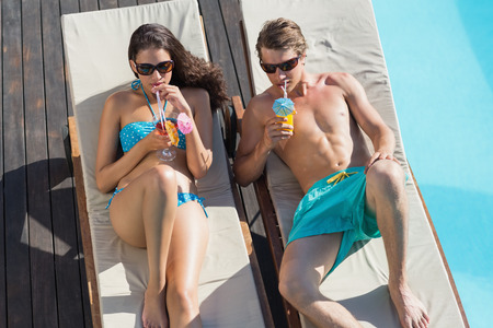 loungers: High angle view of a young couple with drinks on sun loungers by swimming pool Stock Photo