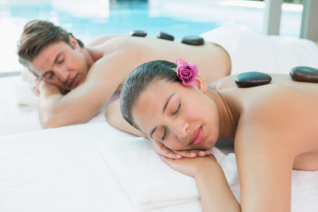 Side view of a young couple enjoying stone massage at health\ farm