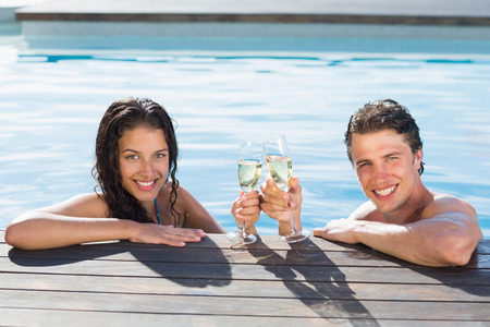 Portrait of a young couple toasting champagne in swimming pool on a sunny day photo