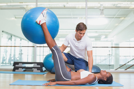 gym ball: Personal trainer working with client holding exercise ball at the gym Stock Photo