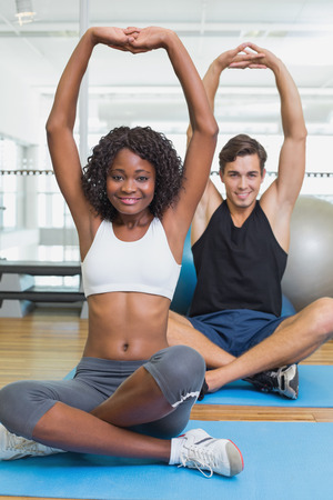Fit couple warming up on exercise mats at the gym photo