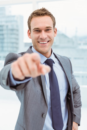 Portrait of smart young businessman in suit pointing at you in office photo