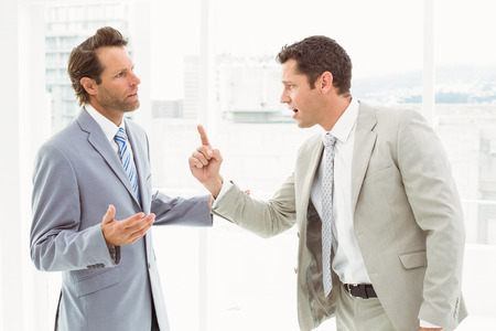 annoy: Business male colleagues in an argument at office