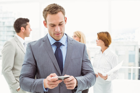 text message: Businessman text messaging with colleagues in meeting behind at office