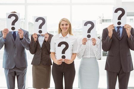 Business people holding question mark signs in front of their faces in office photo