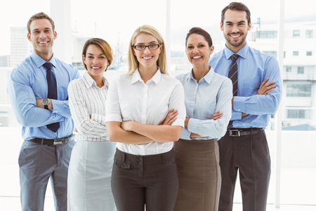 office attire: Portrait of happy young business people with arms crossed in office