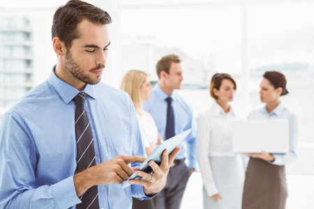 Young businessman using digital tablet with colleagues behind in office photo