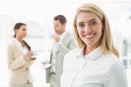 Close up of smiling businesswoman with colleagues behind at office photo