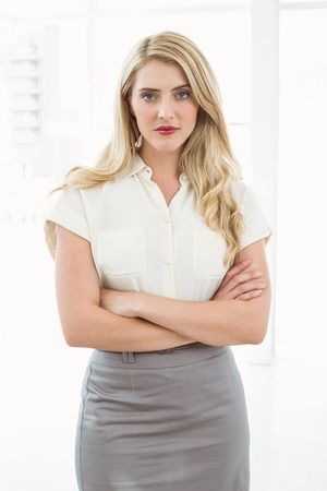 Portrait of beautiful young businesswoman with arms crossed in office photo
