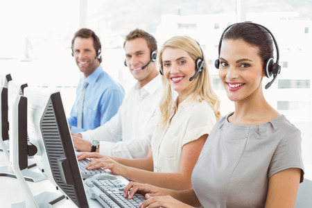 Portrait of young business people with headsets using computers in office photo