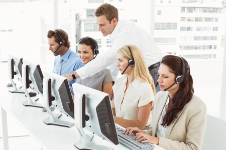 Side view of young business people with headsets using computers in office