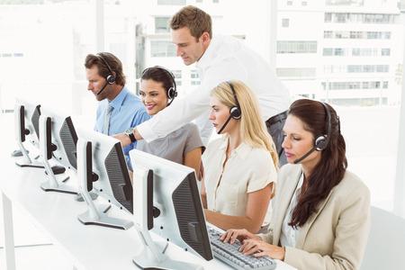 Zijaanzicht van jonge mensen uit het bedrijfsleven met headsets met behulp van computers in het kantoor Stockfoto