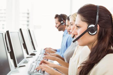 centro de computo: Vista lateral de j�venes empresarios con auriculares que usan ordenadores en la oficina Foto de archivo