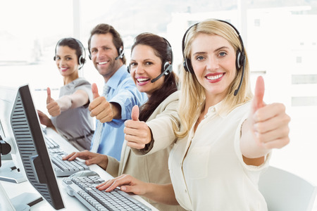 Business people with headsets using computers while gesturing thumbs up in office photo