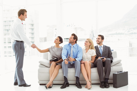 Businessman shaking hands with woman besides people waiting for job interview in office photo