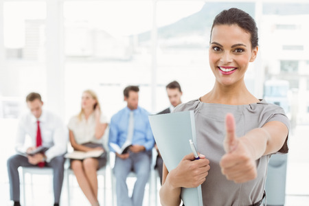 Businesswoman gesturing thumbs up against people waiting for job interview in office