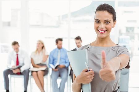 Empresaria que gesticula los pulgares para arriba contra el pueblo esperando la entrevista de trabajo en la oficina Foto de archivo