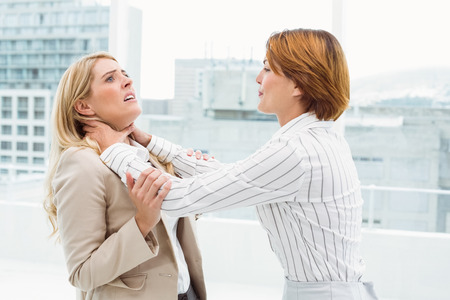Side view of businesswomen having a violent fight in office Stock Photo