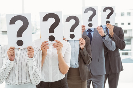question marks: Business people holding question mark signs in front of their faces in office