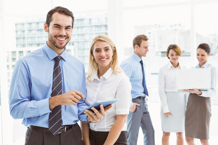 Business couple using digital tablet with colleagues behind in office photo