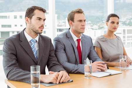 reviewer: Panel of corporate personnel officers sitting at table in office Stock Photo