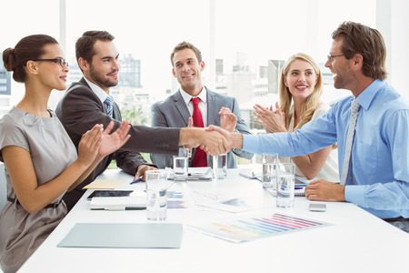 Executives shaking hands in board room meeting at office photo
