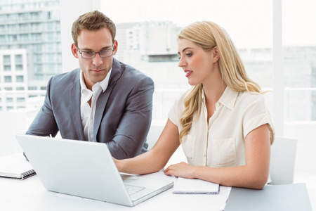 Young business people using laptop in meeting at office photo